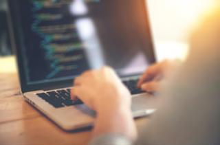 Zdjęcie przedstawia dłonie osoby piszącej na laptopie.