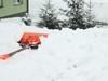 Zdjęcie fragmentu posesji, na której leży śnieg i łopata do odśnieżania.