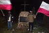 Zdjęcie dwóch mężczyzn przy pomniku w nocy z flagami Polski